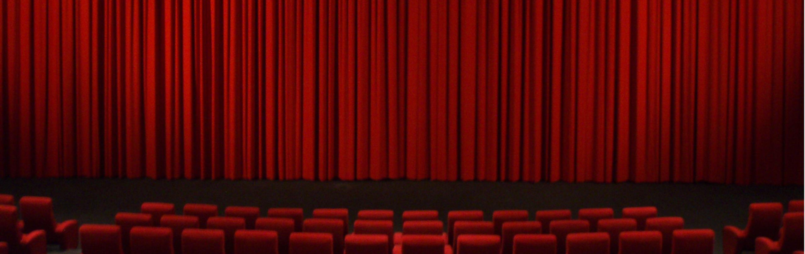 Red curtains and chairs in a movie theater.